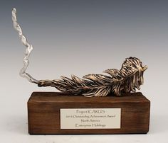 These custom awards were created for the GBTA Foundation, the world's premier business travel organization, as part of their Project ICARUS initiative, which recognizes business travel professionals who are delivering best-in-class sustainability programs across North America. These awards are based on the project's logo - a feather transforming into a flame. They are created from reclaimed pewter, and mounted on wood bases recycled from a local wood tower.