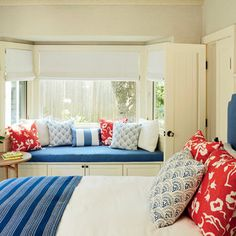 Micek converted a former family room into a sunny blue-and-coral guest room. The window seat cushion and headboard are a chambray linen. The coral pillow fabric is by Victoria Hagan.
