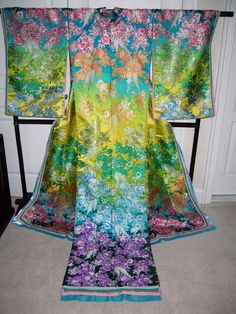 Modern reworking of the wedding kimono with short sleeves and a train. This design is known as mai curren and is inspired by Chinese robes. Mai curren uchikake tend to be very colourful; this one has blossom clusters in rainbow hues.