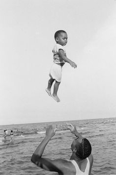 Man tossing a child into the air at 57th Street Beach. Photograph by Stephen Marc, 1988.
