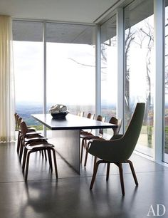 Vintage Arne Jacobsen seating—a set of Grand Prix chairs and a Giraffe armchair—surrounds a minimalist dining table designed by Mori and Peter Superti, which is set into a polished-concrete floor; the centerpiece is a sculpture by Jeff Zimmerman.