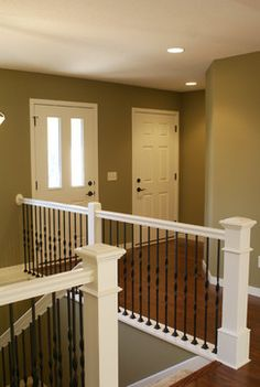 Stair Systems | white staircase with black wrought iron balusters | Bayer Built Woodworks