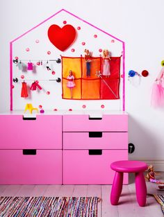 Commode rose adossée à un mur sur lequel est dessinée la forme d'une maison. Un cœur lumineux est fixé au faîte du toit, des poupées sont installées dans un rangement mural à poches et leurs vêtements sèchent à une barre comme à une corde à linge.