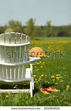 Adirondack chair with summer hat - stock photo