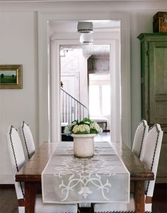 Rustic Dining Room: In this Alabama home, designers Paige Schnell and Doug Davis of Tracery Interiors used white to create a clean look in a casual dining room. A Circa Antiques runner dresses up the farm table.