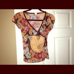 Top Floral top with black and orange under tone. It is 90% polyester and 10% spandex. one clothing Tops Blouses
