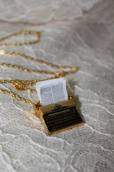 typewriter necklace. I would definitely get a magnifying glass and read what it says! Sthis will be cute present for writer