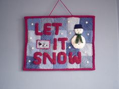 This knitted picture is made like a patchwork quilt. The background is pieced from squares knitted out of oddments of double knitting weight yarn and then knitted letters and decorations are added. A knitted binding frames the picture and also holds the dowel that keeps the whole thing in shape. The finished picture is about 45cm wide and 36.5cm tall. Complete instructions are included for the letters in 'Let It Snow', if you want to use different words other letters can be found in my…