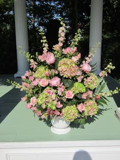 Created with antique green hydrangea pink peonies, pink and ivory roses, pink larkspur, pink alstromeria, and mixed greens.