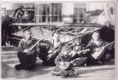 Baby Alexei playing the domra, while the other boys play along on balalaikas, aboard the Standart.