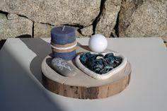 Blue Heart é uma decoração da ArteNatis constituída por:  - Uma base em forma de tronco de árvore;  - Uma vela decorativa azul, realçada com uma fita de serapilheira e uma trança de cordas brancas de algodão;  - Uma vela esférica branca;  - Uma pedra acastanhada decorada com uma pintura realizada à mão, com tinta branca;  - Um elemento em forma de coração, delimitado por uma corda espessa branca e preenchido por pot-pourri de tons azuis.