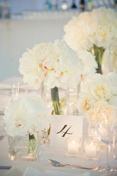 Wedding Decor Inspiration: All-white floral centerpieces and small tealight candles create an elegant, yet intimate scene