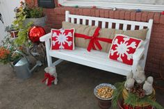 Front porch idea--love the burlap with snowflake pillows, and squirrel figures with pinecones.