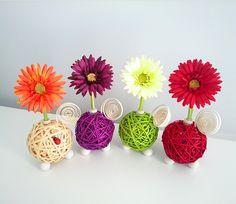 Centro Floral Aromático Flowerfresh modelo Ball. Bola central de 4 colores hecha de tiras de ratán. Cuentan con complementos como espiral y mariquita de madera. Además puedes elegir entre 4 colores de flor y el aroma a evaporar.