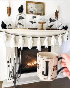 how cool is this halloween mantel with bats in cloches and a ghost garland?! plus that #anthropologie mug is just too cool!