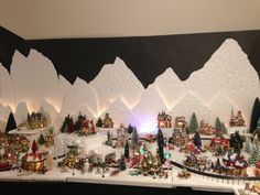 Christmas Village- North Pole. I carved the mountains with a hotwire foam factory tool out of styrofoam. I mounted extra village lights between the sheets to add dimension and a light effect. 2015 North Pole.