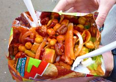 TOSTILOCOS recipe: cut bag of  Tostilocos brand chips lengthwise, top with diced cucumber, diced jicama, diced tomatoes, Japanese peanuts, chaca-chaca candy, cueritos (pickled pork rinds), Valentina brand hot sauce and Chamoy. There you have some delicious Mexican street food.