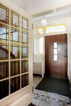 Jaren30woningen.nl | Stijlvolle vestibule met authentieke voordeur, tegelvloer en glas in lood deur