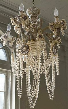 Drape pearls on a vintage chandlier for a shabby chic look. This is pretty cool...