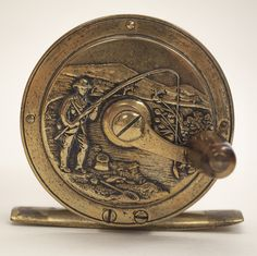 Birmingham Fly Reel, Maker Unknown. Accession No. 1986.028.261.  Diameter 2 1/2 inches, pillar length 1 inch, weight 6 ounces. This attractive reel, featuring bas relief angling scenes on the plates, was commercially produced in at least two sizes, both as a crank handle reel and as a revolving plate reel.  It appears to be a Victorian era British product.  The design was reproduced in Germany during the 1970s and it is now difficult to differentiate the original reels from the reproductions.