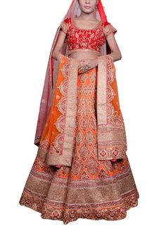 Saroj Jalan presents a gorgeous ornate lehenga in an orange hue. The voluminous raw silk orange lehenga has red patchwork embroidery all over and a wide golden border flanked by an orange and red scalloped border. It has been teamed with an all over embroidered orange raw silk blouse. An orange net dupatta with red patch embroidery completes the look. As an additional ornament, the set features a red stole with all over buti design and a contrasting embellished border.