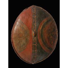 BOUCLIER, MASAÏ, KENYA A MAASAI SHIELD, KENYA en cuir tanné et peint, de forme ovale, convexe. La face, divisée par une bande centrale, est ...