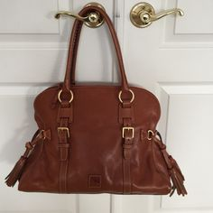 Dooney Bourke leather handbag Donkey Bourke Authentic real leather handbag; beautiful cognac color; structured with two side tassels; 4 feet at bottom; great condition Dooney & Bourke Bags Shoulder Bags