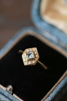 A truly stunning ring, this 14k solid gold piece features an amazing geometric art deco-era design and princess cut aquamarine. Lined with diamonds that measure 1.5 mm each (making the total about .15 carats), this ring is Danish in origin from about the 1940s. The aquamarine has a beautiful regal blue tone and is eye clean, it measures about 5x5mm and is bezel set. The diamonds are about F in color.