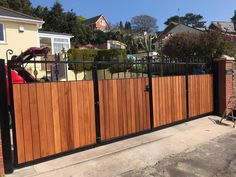 Bi-Fold Driveway gates. A great solution for those with limited return wall space. This example, the Wilton has a total of four gate sections. Constructed using Iroko hardwood.