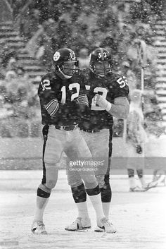 Quarterback Terry Bradshaw #12 of the Pittsburgh Steelers huddles near center Mike Webster #52 as snow falls during a game against the Baltimore Colts at Three Rivers Stadium on December 9, 1978 in Pittsburgh, Pennsylvania.