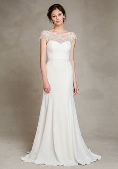 The Hayden in our luxurious crepe offers clean, elegant lines in a fit and flare silhouette which elongates the bride's figure. Sheer Marseille embroidered lace trims the bodice creating bateau neckline and dramatic V-back. A sweeping train completes this classic look. The dress is fully lined with a center-back invisible zipper. (A bustle can be added by a seamstress).