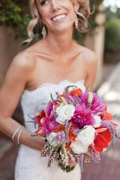 Gorgeous hot pink, orange, and coral bridal bouquet featuring ranunculus, tulips, and dahlias.