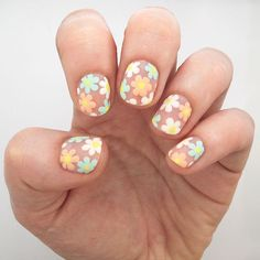 Put a twist on your typical flower nail art with a design built on a blank background for an airy appearance. If you can make dots, you can pull off these flower nails! - DivineCaroline.com