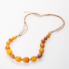 Honey toned agate stones wrapped in wire on a brown leather cord create this bright chic necklace.