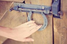 Barn door latch made of horse shoe.