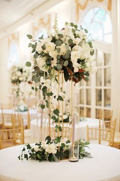 tall lush wedding reception arrangement in all white flowers and greenery. white garden roses, ranunculus, tulips, spray roses, hydrangea, larkspur and veronica flowers are combined with magnolia, eucalyptus and vines. a cluster of flowers and greenery sits at the base of the gold pedestal, surrounded by brass candlesticks with pale grey taper candles.