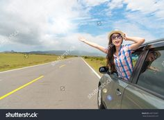 elegant woman wearing hat and sunglasses happily looking out car window open arm enjoying sunshine holiday on asphalt road background.
