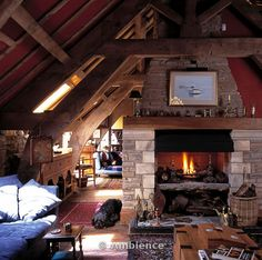 Ambience Images | Barn conversion living room with lighted fire in stone fireplace