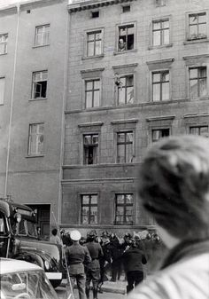 Four-year-old Michael Finder of East Germany is tossed by his father into a net held by firemen across the border in West Berlin. The apartments were in East Berlin while their windows opened into West Berlin, October 7, 1961 -