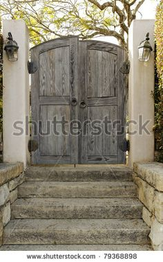 A weathered wooden gate with lamps on each side is closed barring the entrance to someone's property. Vertical shot. by Portlandia, via ShutterStock
