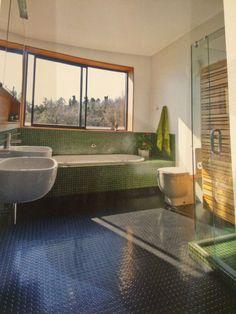 Green mosaics in bathroom, wooden vertical storage.