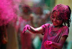 """An Indian girl, her face smeared with colored powder, reacts as water is squirted on her during Holi celebrations in Chennai, India, on March 8, 2012. (AP Photo/Arun Sankar K.)"""