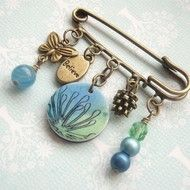 This pretty brass kilt pin brooch features a handmade polymer clay charm, together with brass charms and glass beads. The polymer clay charm is inked in blue and green, and stamped with a delicate flower image - it measures 2cm across. The pin is 5cm l...