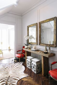 Susan Greenleaf San Francisco Home - A wooden entryway console with twin mirrors, armchairs and stools; a zebra rug; and herringbone floors