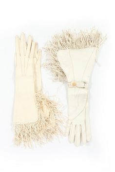 A large group of leather gloves, 1930s-50s. including a pale duck-egg blue pair with acorn shaped tassels; two white western-style pairs with fringing; a pale lavender suede example and others