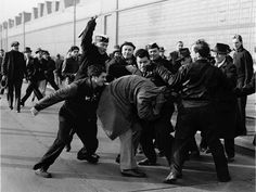 """The Picket Line"" - It was April 3, 1941, day 2 of the first United Auto Workers' strike at the Ford Motor Co. factory. The factory was closed; 120k workers were idle. Tensions ran high. Fists were clenched, clubs rose, and 8 strikers turned on a lone dissenter, crouching low, coat over his head. The camera under his coat, Brooks ducked into the crowd. ""A lot of people would have liked to wreck that picture."" Brooks was later awarded a Pulitzer Prize for the photo.  Photo credit: Milton…"