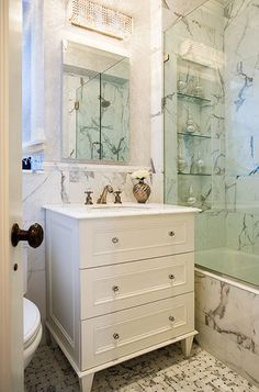 gorgeous small white bathroom design with white bathroom vanity with white calcutta marble countertop, glass knobs, brushed nickel faucet, calcutta marble backsplash & shower surround, glass shower, calcutta marble basketweave tiles floors, crystal sconce.