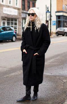Always Judging in a heavy black coat and dark sunglasses
