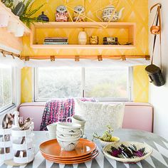 Small-space wizardry: Make a tight space (this one a trailer) feel airy with a patterned, sunny yellow stenciled statement wall.