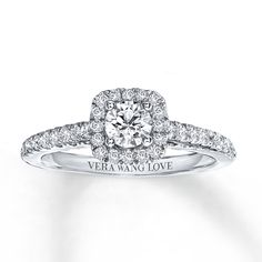 From the Vera Wang LOVE Collection, this captivating engagement ring features a mesmerizing 1/3 carat round center diamond surrounded by a frame of smaller accent diamonds. Additional diamonds grace the ring's band on all sides, ensuring sparkle from every angle. Set into the bezel are two princess-cut sapphires, the signature of the collection and a symbol of faithfulness and everlasting love. Styled in 14K white gold with 3/4 carat total weight of diamonds, the ring is a brill...